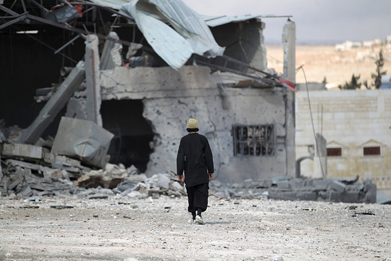 A man inspects a site hit by what activists said were airstrikes carried out by the Russian Air Force in the town of Babila, in the southern countryside of Idlib, Syria (Reuters)