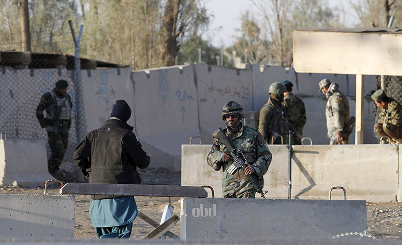 Afghan security forces stand guard at the entrance gate of Kandahar Airport where Taliban stormed on late Tuesday, in Kandahar, Afghanistan December 9, 2015