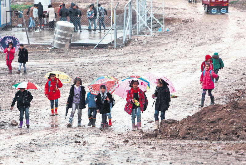 Refugee children hold umbrellas as they go to school on a rainy day in Arbil November 9, 2015.
