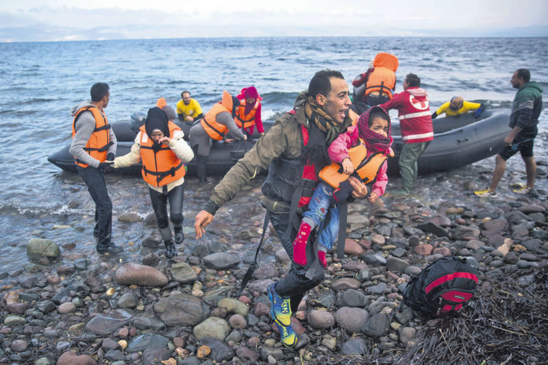 A man and a child after their arrival on a raft from the Turkish coast to the Greek island of Lesbos.