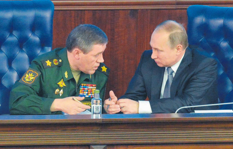 Russian President Putin (R) talks with the Chief of Russian army general staff Gerasimov (L), during a Defence Ministry board meeting in Moscow on Friday.
