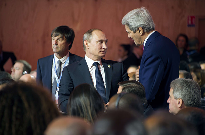 US Secretary of State John Kerry (Right) talks with Russian President Vladimir Putin (C) during the opening day of the World Climate Change Conference 2015 (AFP Photo)
