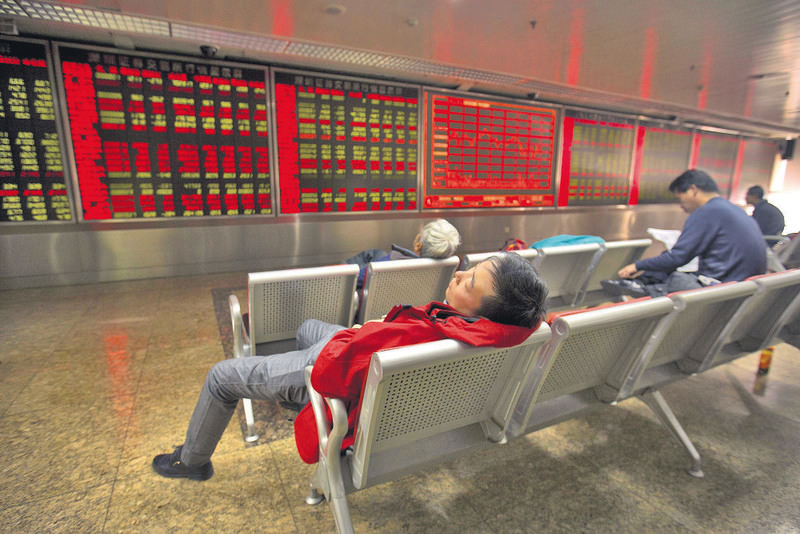 A Chinese investor naps while monitoring stock prices at a brokerage house in Beijing, Friday, Dec. 4, 2015.
