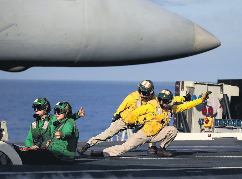 A flight deck crew prepares to launch an F18 Super Hornet from the deck of the US Eisenhower off the coast of Virginia, December 10, 2015 in the Atlantic Ocean.