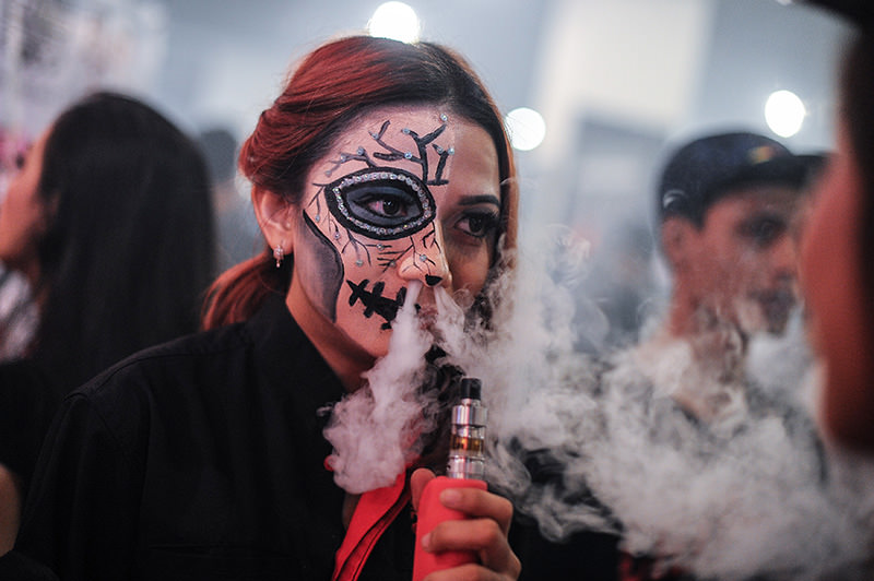 A promoter with a painted face smokes an electronic cigarette during the VapeFair in Kuala Lumpur on December 5, 2015. (AFP Photo)