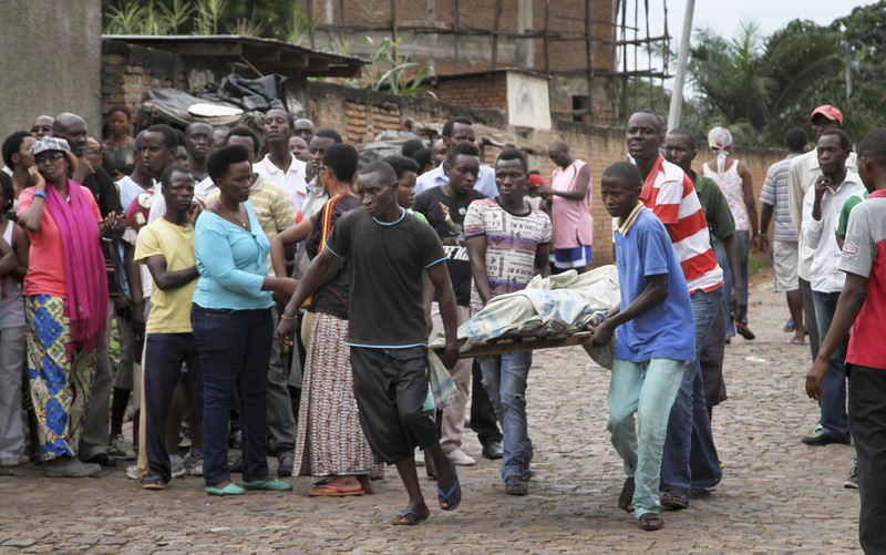 Men carry away a dead body in the Nyakabiga neighborhood of Bujumbura, Burundi, Saturday, Dec. 12, 2015 (AP Photo)
