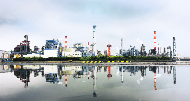A petrochemical plant is reflected in a puddle at an industrial complex in Kawasaki near Tokyo. (Reuters Photo)