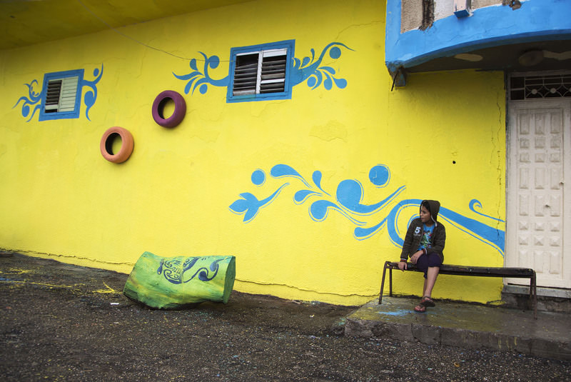 A Palestinian boy sits outside his family house that was painted by Palestinian artists in the al-Shati Refugee Camp in Gaza City, Tuesday, Nov. 17, 2015. (AP Photo)