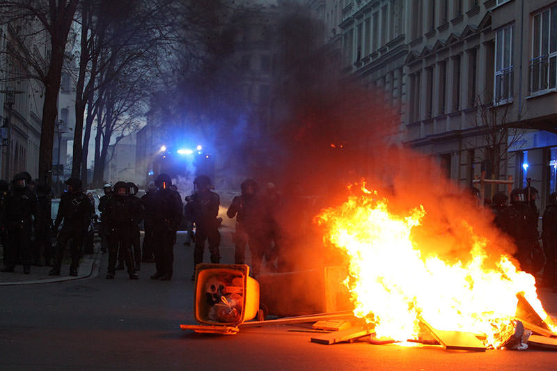 Police officers stand by burning containers as they face leftist group members who were demonstrating against a rally of anti-immigrant group on Dec 12, 2015 in Leipzig, Germany (AFP photo)