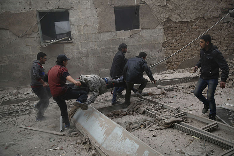 Syrians evacuate victims following air strikes on the town of Douma in the eastern Ghouta region, opposition stronghold east of Damascus, on Dec 13, 2015 (AFP photo)