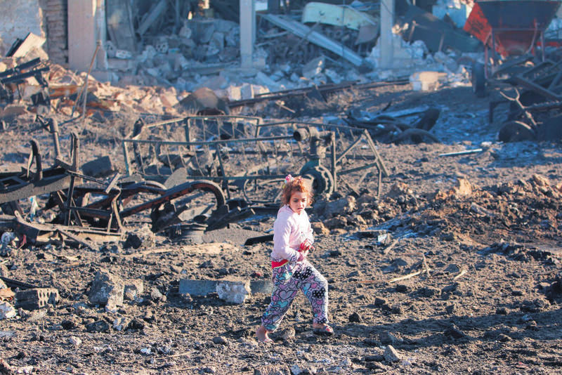 A girl walking over debris at a site hit by one of DAESH's triple truck bombs in the YPG-controlled town of Tel Tamer, Syria.