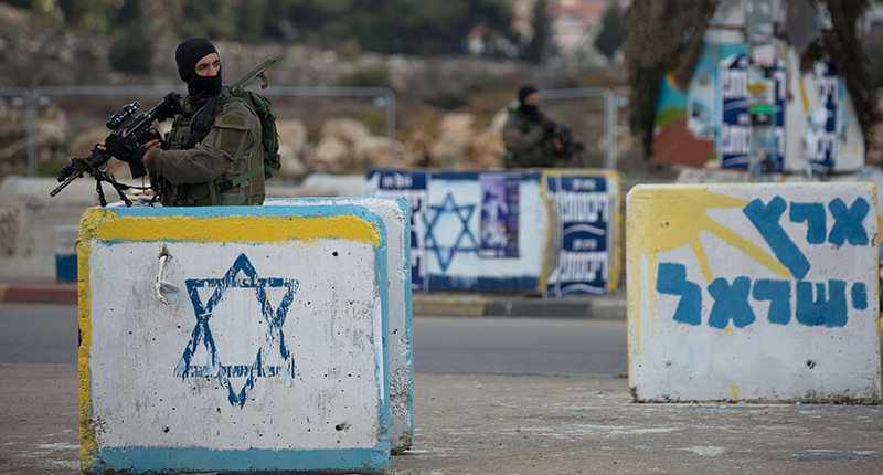An Israeli soldier from the elite infantry unit stands guard at the Gush Etzion junction in the Israeli occupied on the main road between Jerusalem and Hebron on December 2, 2015 (AFP Photo)