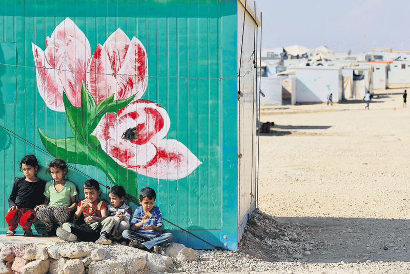A group of Syrian refugees posing in front of their family's painted caravan at Al Zaatari refugee camp, in Mafraq city of Jordan near the border with Syria