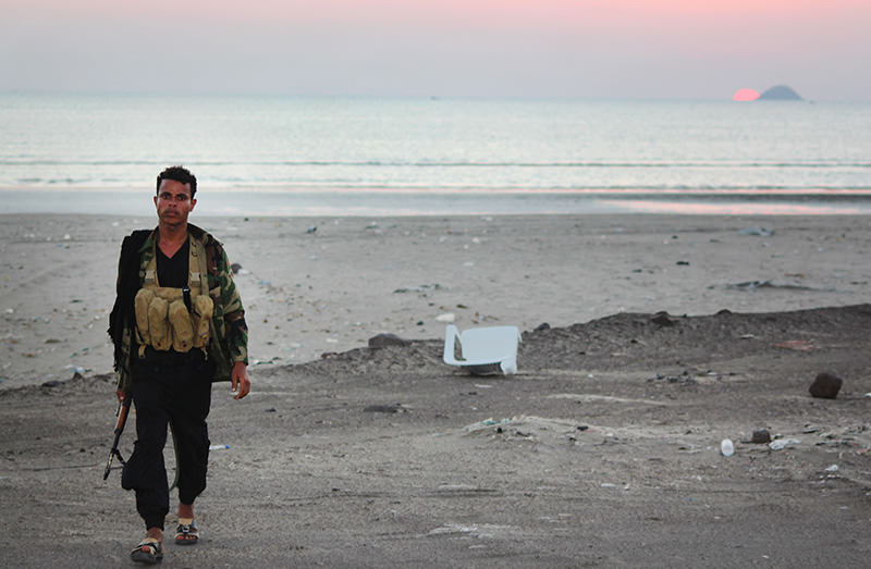 A Yemeni fighter loyal to Yemeni President Abedrabbo Mansour Hadi walks at the beach in Dabab district in Taez province, on Dec 13, 2015 (AFP photo)