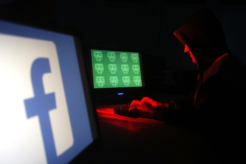 Man poses in front of on a display showing a Facebook logo and the word 'cyber' in binary code, in this picture illustration taken in Zenica December 27, 2014 (Reuters Photo)