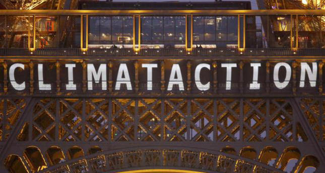 The slogan ''Climate action'' is projected on the Eiffel Tower as part of the World Climate Change Conference 2015 in Paris, December 11, 2015. (REUTERS Photo)