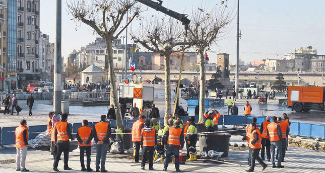 Workers planted the first trees in the square on Monday.