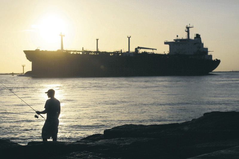 An oil tanker heading for the Port of Corpus Christi passes a fisherman as it enters a channel near Port Aransas, Texas.