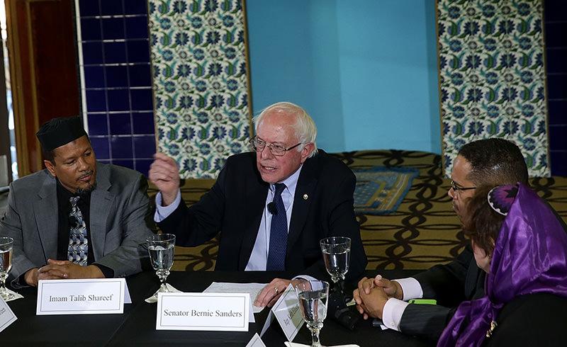 Democratic presidential candidate Sen. Bernie Sanders (I-VT) (3rd L) speaks as (L-R) Rev. Reginald Green, Imam Talib Shareet, Rep. Keith Ellison (D-MN) and Rabbi Batya Steinlauf listen at Masjid Muhammad (AFP Photo)