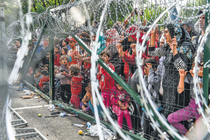 Refugees stand behind a fence at the Hungarian border with Serbia near the town of Horgos on Sept. 16.