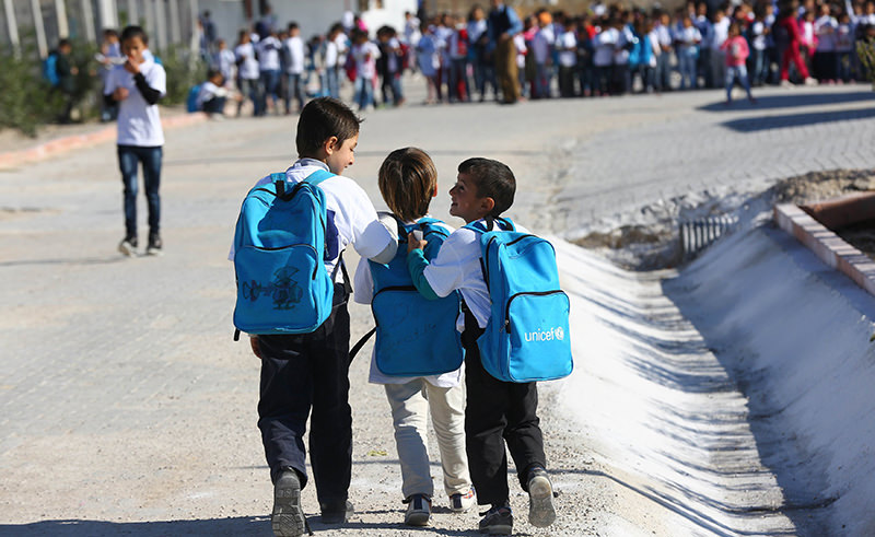 Syrian Refugee children walk past carrying backpacks outside their school at the refugee camp in Osmaniye on December 15, 2015. (AFP Photo)