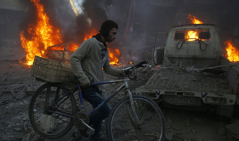 A man carries his bicycle past debris and burning cars following reported airstrikes in the town of Hamouria, Syria (AFP Photo)