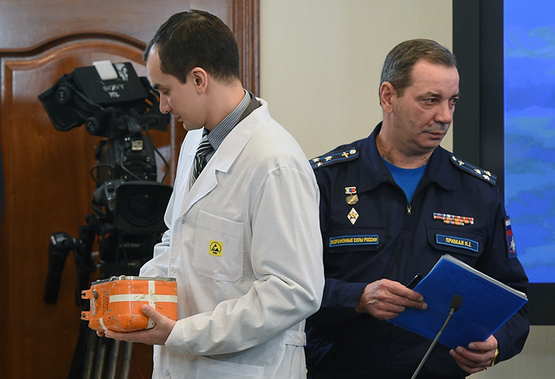 A specialist takes away the flight recorder from the Russian Sukhoi Su-24 bomber in Moscow on December 18, 2015 (AFP photo)