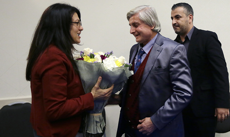 Syrian refugee Refaai Hamo, center, is greeted by Michigan State Rep. Rashida H. Tlaib at a news conference, Thursday, Dec. 17, 2015, in Romulus, Mich.  (AP Photo)