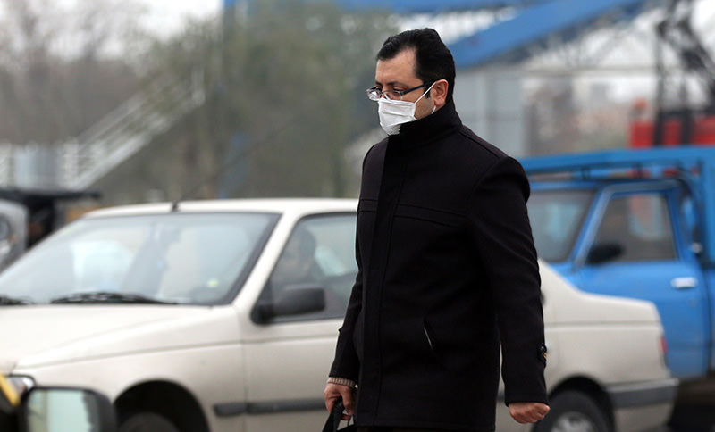An Iranian man wears a facemask as he walks in a heavily polluted area in the west of the capital Tehran, on December 14, 2015. (AFP Photo)