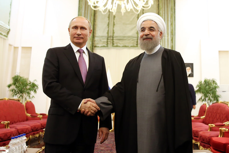 Russian President Vladimir Putin, left, shake hands with Iran's President Hassan Rouhani at the start of their meeting during the Gas Exporting Countries Forum. (AP Photo)