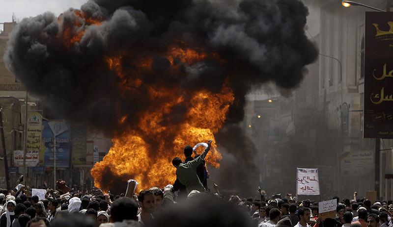 Yemeni anti-government demonstrators react after setting on fire a vehicle belonging to supporters of President Ali Abdullah Saleh during clashes in Sanaa. (AP Photo)