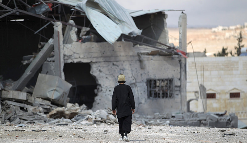 A man inspects a site hit by what activists said were airstrikes carried out by the Russian air force in the town of Babila, in the southern countryside of Idlib, Syria, October 7, 2015 (Reuters Photo)