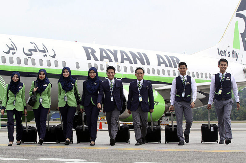 A picture made available on 21 Dec 2015 shows Rayani Air Malaysia's first Islamic-compliant airline cabin crew posing for photo in front of Boeing 737-400 (EPA photo)