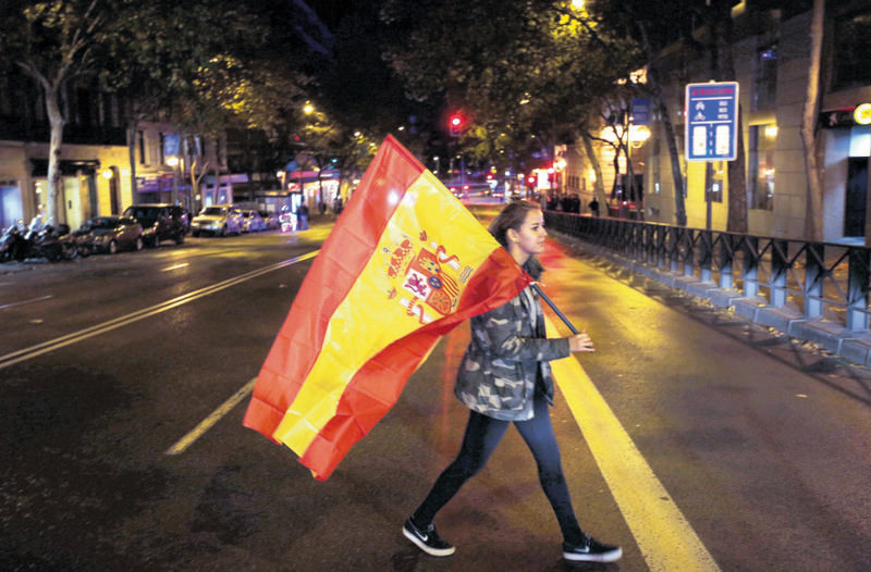 A supporter of the Popular Party carries a Spanish flag as she leaves the party headquarters in Madrid on Sunday.