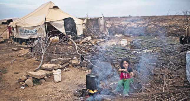 Syrian refugee Aysha Elwan, 5, helps her mother break wood to add to the fire to boil water outside her family's tent at an informal tent settlement on the outskirts of Mafraq, Jordan.