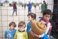 Chıldren stand next to a fence as mıgrants and refugees waıt ın a camp to regıster after crossıng the Macedonıan-Greek border near Gevgelıja on Sep 16, 2015. (AFP Photo)