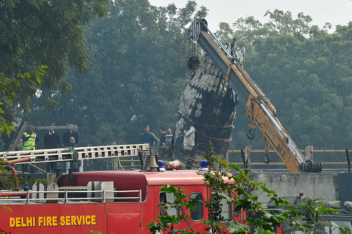 A piece of plane wreckage is hoisted by a crane as rescue personel look on at the crash site of a chartered army plane close to the main airport in New Delhi on December 22, 2015 (AFP Photo)