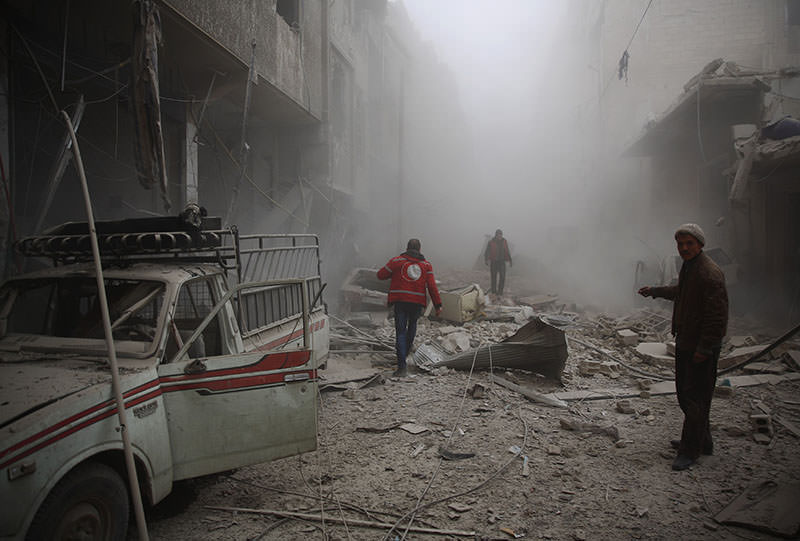 Members of the Syrian Arab Red Crescent search for survivors amid the rubble of destroyed buildings following air strikes in opposition-held town of Douma, in Syria, on Dec 13, 2015 (AFP photo)