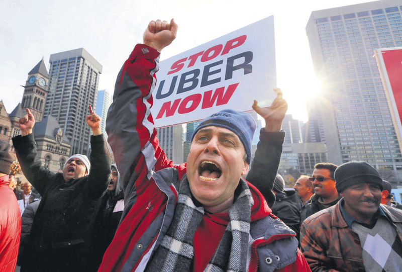 Taxi drivers protest in front of city hall against the Uber ridesharing car service in Toronto.
