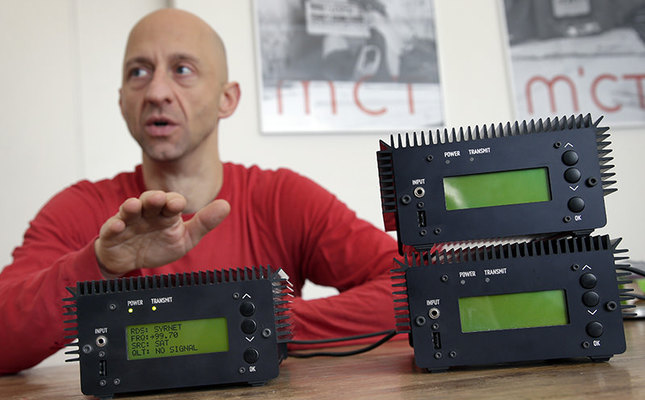 Philipp Hochleichter of the MICT organization talks behind Pocket FM Radio Transmitters in Berlin, Germany. As part of the Syrian radio networking project, MICT has designed small modular FM transmitters. (AP Photo)
