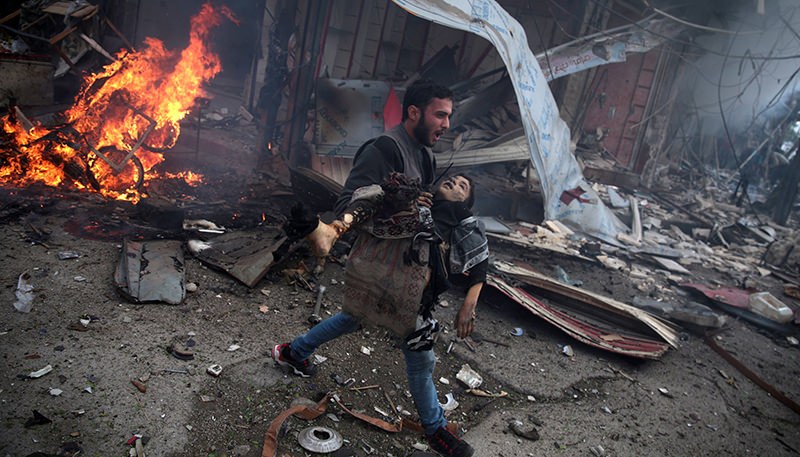 A Syrian man carries the body of a child killed in a reported air strike by government forces in the rebel-held area of Douma, east of the capital Damascus, on November 7, 2015.  (AFP Photo