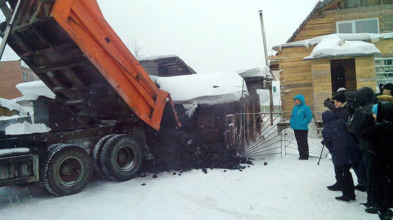In this photo taken on Dec. 23, 2015, Yelena Salnikova gets a truck full of coal from authorities for losing 30 kilos in weight.