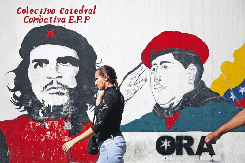 A woman walks past a mural depicting Cuban revolutionary hero Ernesto ,Che, Guevara (L) and Venezuela's late President Hugo Chavez near the National Assembly building in Caracas, Venezuela.