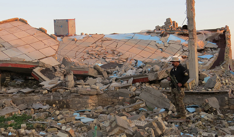 A member of the Iraqi security forces stands in the rubble of destroyed buildings in the rural Husayba al-Sharkiya area, east of Anbar province's capital Ramadi (AFP Photo)