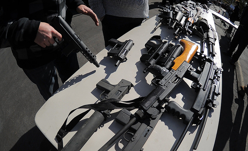 An LAPD officer stands before collected assault weapons during the LAPD Gun Buyback Program event in the Van Nuys area of north Los Angeles, on December 26, 2012 (AFP Photo)