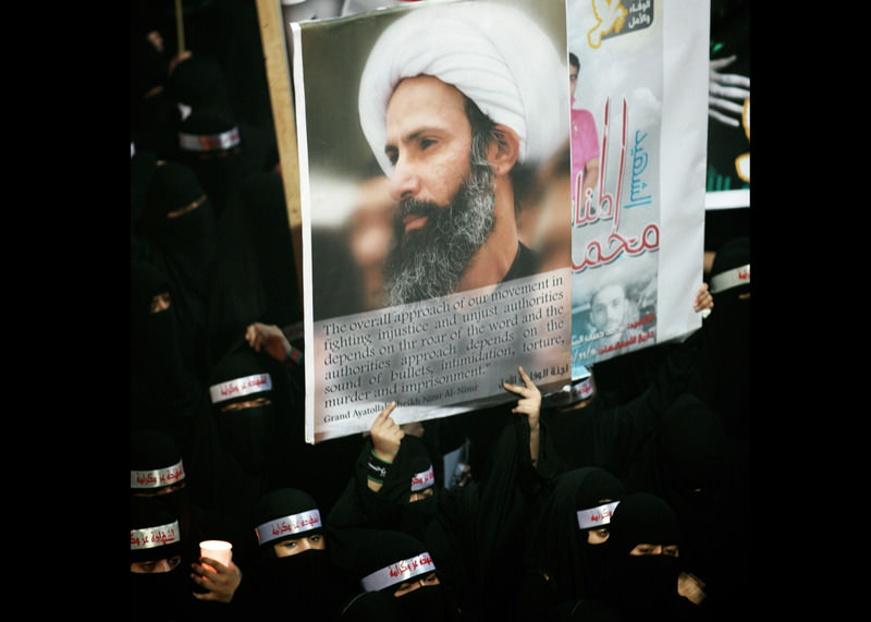 In this Sunday, Sept. 30, 2012 file photo, a Saudi anti-government protester carries a poster with the image of Shiite cleric Sheik Nimr al-Nimr (AP Photo, File)
