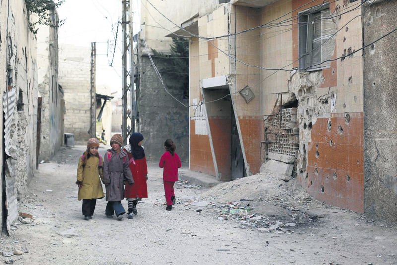 Syrian children walk through a moderate-held area of Douma on the outskirts of Damascus, Syria.