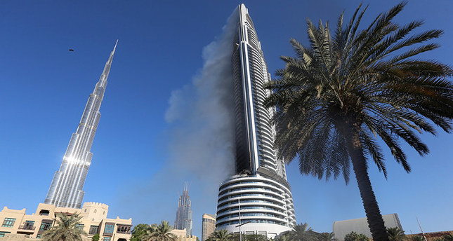 Plumes of smoke rise from the 63-storey Address Downtown Dubai hotel and residential block near the Burj Khalifa, the tallest building in the world, a day after the hotel caught fireemReuters Photo/em