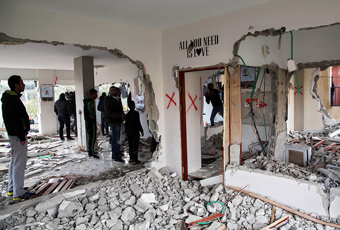 Palestinians stand inside a house that was demolished by the Israeli military in the east Jerusalem neighborhood of Jabal Mukaber, Monday, Jan. 4, 2016 (AP Photo)