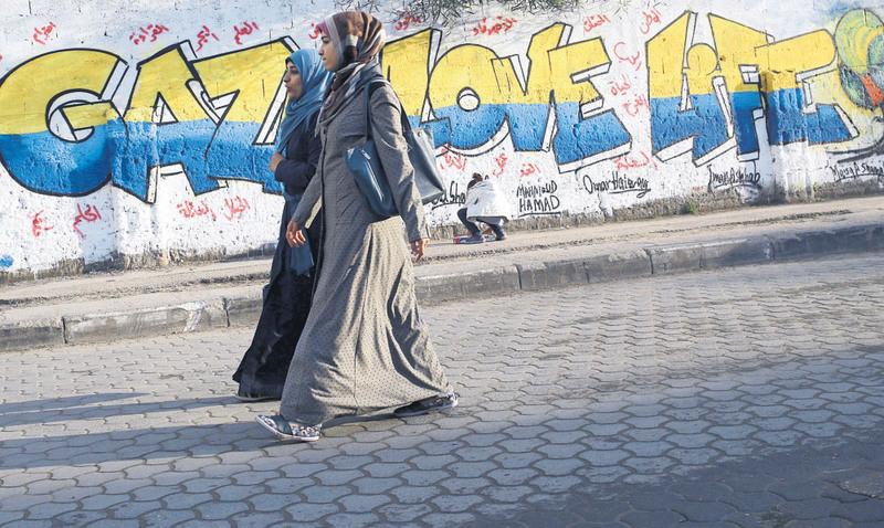 Two female Palestinian students walking past a graffiti reading ,GAZA LOVE LIFE, in Gaza City, on Dec. 30, 2015.